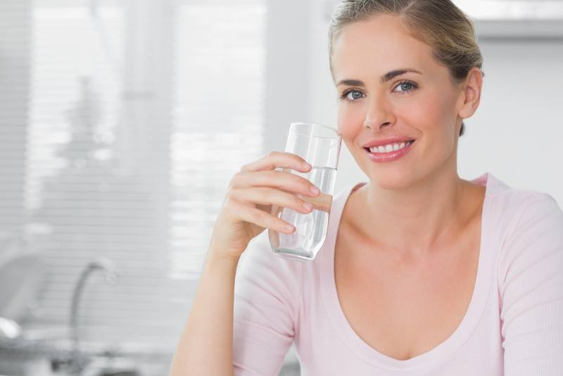 Beautiful woman drinking a glass of pure drinking water in her kitchen